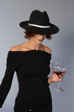 Woman with black dress and wine and mafia hat. Brunette woman standing with black dress and mafia hat, holding a glass of wine Royalty Free Stock Image