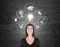 Woman in black and education icons. Smiling woman in black is standing near chalkboard with education icons on it. Concept of knowledge gaining stock images
