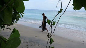 Woman in black elegant dress, walking on beautiful beach. Woman in elegant black dress walking by the sea in Gili Air island, Indonesia stock video footage