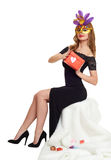 Woman in black evening gown and carnival mask with gift box. Sit on white fur. Valentine holiday and party concept. Woman in black evening gown and carnival Royalty Free Stock Photos
