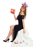 Woman in black evening gown and carnival mask with gift box. Sit on white fur. Valentine holiday and party concept. Woman in black evening gown and carnival Royalty Free Stock Images