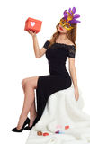 Woman in black evening gown and carnival mask with gift box. Sit on white fur. Valentine holiday and party concept. Woman in black evening gown and carnival Stock Photos