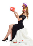 Woman in black evening gown and carnival mask with gift box. Sit on white fur. Valentine holiday and party concept. Woman in black evening gown and carnival Royalty Free Stock Image