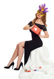 Woman in black evening gown and carnival mask with gift box. Sit on white fur. Valentine holiday and party concept. Woman in black evening gown and carnival Stock Image