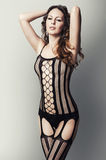 Woman in black fishnet body stocking suit Stock Photography