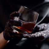 Woman in black glass of whiskey Royalty Free Stock Photography