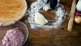 Woman in black gloves is cutting dough for cooking pie with meat stock video footage