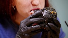 A woman in black gloves taking black burgers and eating it stock footage