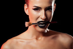 Woman with black and gold make up bitting a make up brush Royalty Free Stock Photography