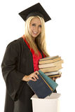 Woman in black graduation gown books into garbage Royalty Free Stock Photos