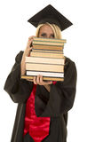 Woman in black graduation gown look over stack of books Royalty Free Stock Images