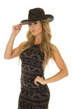 Woman in black and gray dress hand on cowgirl hat Stock Photo