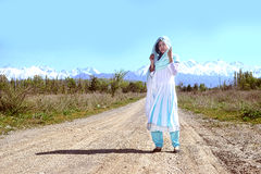 Woman with black hair in blue sari, on the rular road,  nature Royalty Free Stock Photos