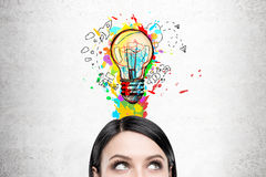 Woman with black hair and colorful light bulb Stock Photo