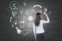 Woman with black hair is drawing dollar light bulb Stock Photo