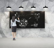 Woman with black hair is drawing sketch in dark concrete room wi. Dark concrete room with blackboard and lamps. Businesswoman is drawing a large sketch with royalty free stock photos