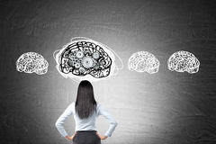 Woman with black hair with four brain and gears sketches Stock Photo