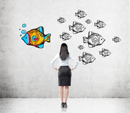 Woman with black hair is looking at fish Royalty Free Stock Images