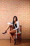 Woman with black hair sits on chair Royalty Free Stock Photography