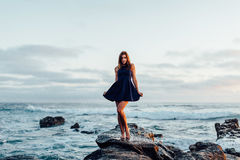 Woman in Black Halter Mini Dress Standing on Brown Rock Royalty Free Stock Image