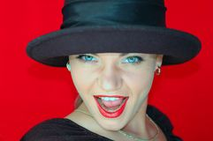 WOman in black hat. Red background Stock Images
