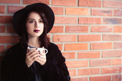 Woman in black hat and coat Stock Photos