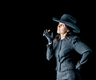 Woman in Black Hat and Dress with Cigar. Brunette woman in black dress, black gloves, and wearing a black cowboy hat standing in front of a black backdrop Stock Images