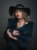 Woman in black hat and fur on a dark background studo shot photo Stock Photo