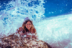 Woman in Black Hat Smiling Widely on Stone With Waves on Her Back Royalty Free Stock Photo