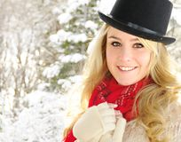 Woman in black hat and snow. Beautiful blonde woman in snow in black hat Royalty Free Stock Image