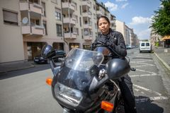 Woman with a black helmet on a motorbike royalty free stock images
