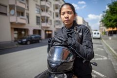 Woman with a black helmet on a motorbike royalty free stock image