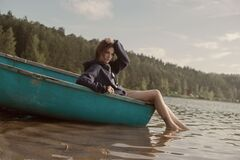 Woman in Black Hoodie in Teal Canoe in Body of Water Royalty Free Stock Photos
