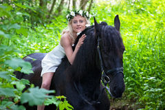 Woman on a black horse Stock Images