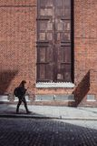Woman in Black Jacket and Black Pants Walking Along the Road Near the Brown Bricked Building Royalty Free Stock Photos