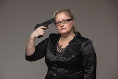 A woman in a black jacket with a black pistol Stock Photo