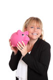Woman in a black jacket holding a pink piggy bank Royalty Free Stock Image