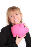 Woman in a black jacket holding a pink piggy bank Royalty Free Stock Images