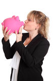 Woman in a black jacket holding a pink piggy bank Stock Image