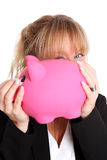 Woman in a black jacket holding a pink piggy bank Stock Photos