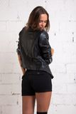 A woman in a black jacket stands back and looks at the floor. White brick wall, not isolated Stock Photography