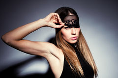 Woman with black lace. Young blond woman with black lace over eyes portrait, studio shot, horizontal Stock Photography