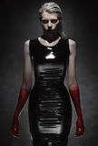 Woman in black latex dress. Portrait of pale woman in black latex dress Royalty Free Stock Images