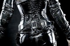 Woman in black latex uniform. Corset, back stock image