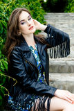 Woman in black leather jacket. Glamorous young woman in black leather jacket outdoors royalty free stock photo