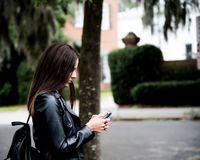 Woman in Black Leather Jacket Holding Smartphone Stock Photos