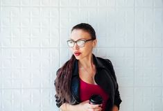 Woman in Black Leather Jacket Wearing Eyeglasses Holding Coffee Cup royalty free stock photography