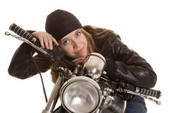 Woman black leather motorcycle lay look. A woman in her leather jacket with a smile on her motorcycle royalty free stock photo