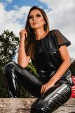 Woman in Black Leather Pants Sitting on Log Stock Images