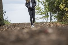 Woman in Black Leggings While Walking on Brown Road Stock Images